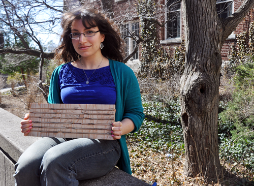 Laura Benakoun holds core samples from tree trunks.