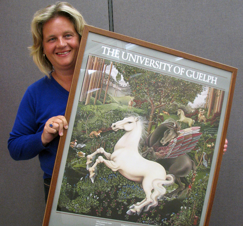 Kim Best with a newly framed U of G poster from the early 1980s.