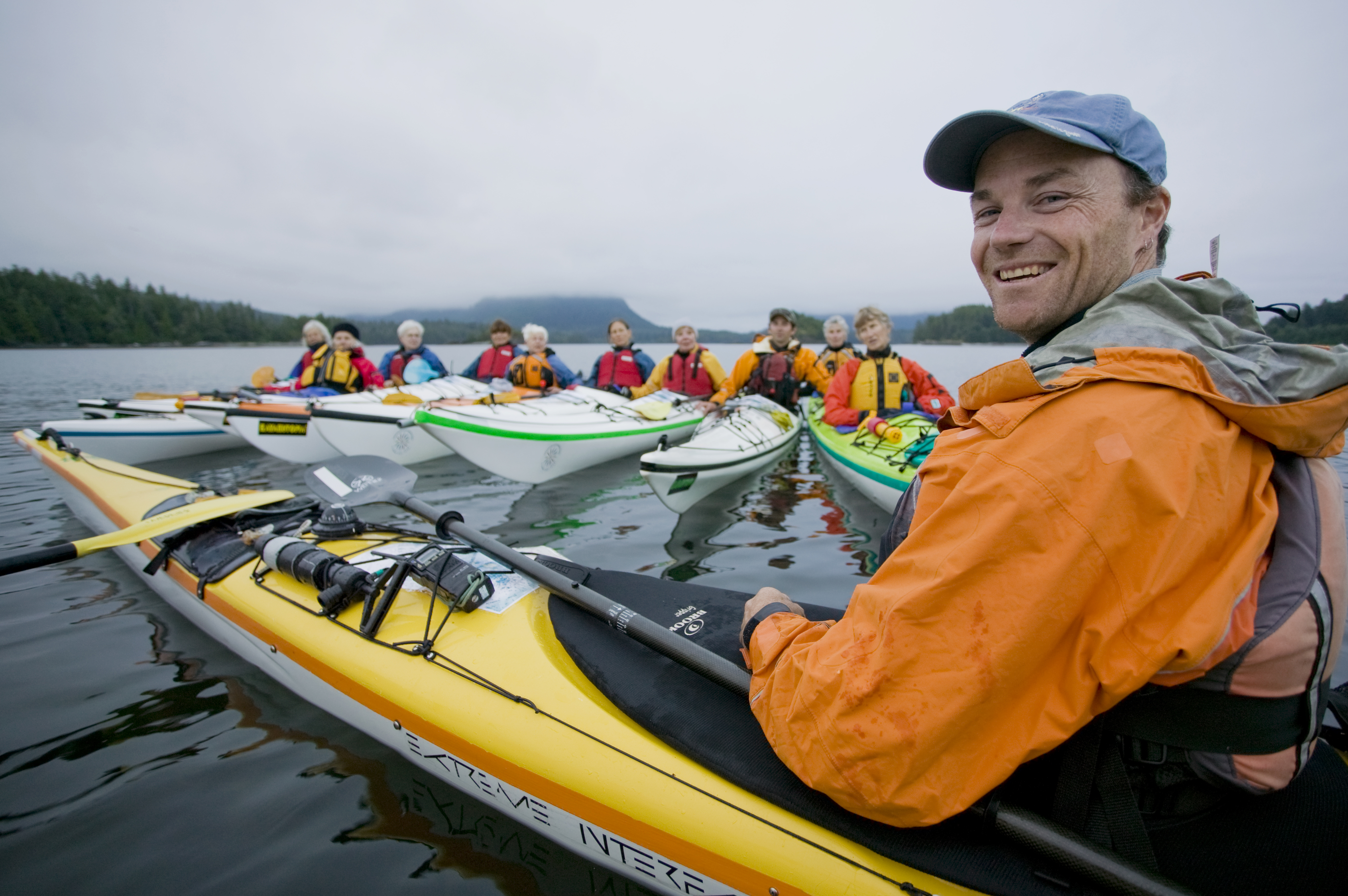 A Kayak guide gives instruction to a group of senior paddlers exploring the area around Spring Island in the Kyuquot Sound area of Northern Vancouver Island. Spring Island, Kyuquot Sound, Vancouver Island, British Columbia, Canada.