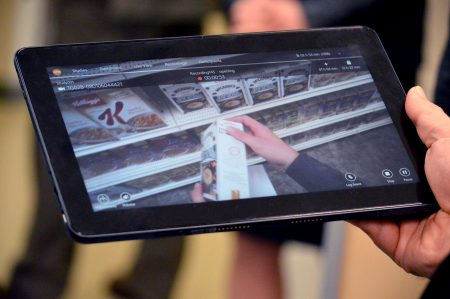 Hand holds a tablet playing video feed of consumer shopping