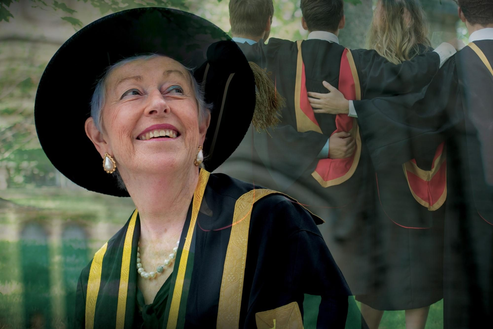 U of G chancellor, Martha Billes, in cap and gown looks up at four students in convocation gowns
