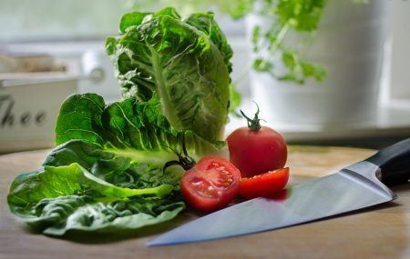 lettuce and a cut-up tomatoe sitting next to a knife