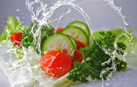 cucumbers, tomatoes and leafy greens being splashed with water