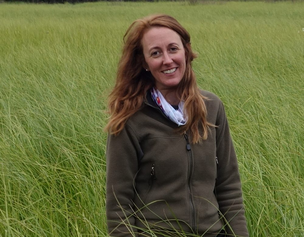Merritt Turetsky standing, smiling in a green field