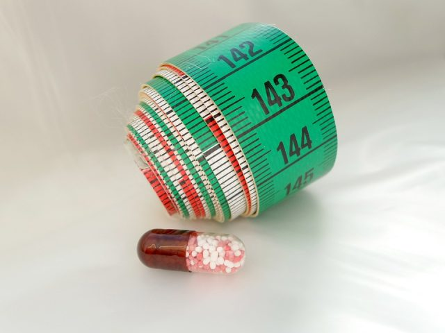 measuring tape rolled up and a pill