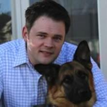 headshot of Prof. Jason Coe with a dog