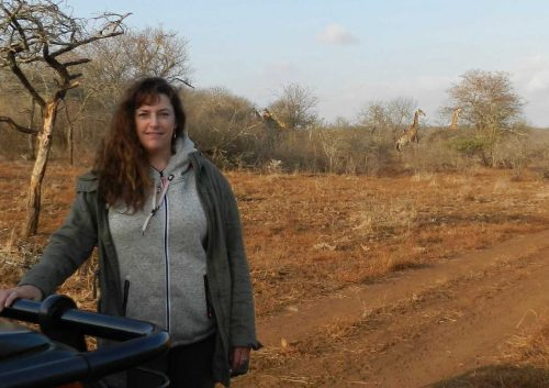 Prof Laura Graham on a game reserve with giraffes in the background