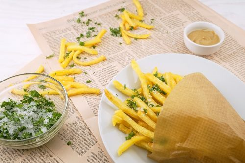 french fries falling out of paper cone onto plate and newspaper resting on table