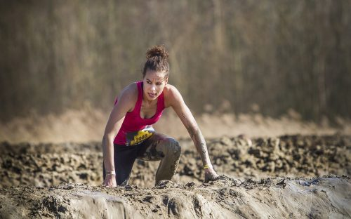 Woman climbing over a mud wall in an obstacle course