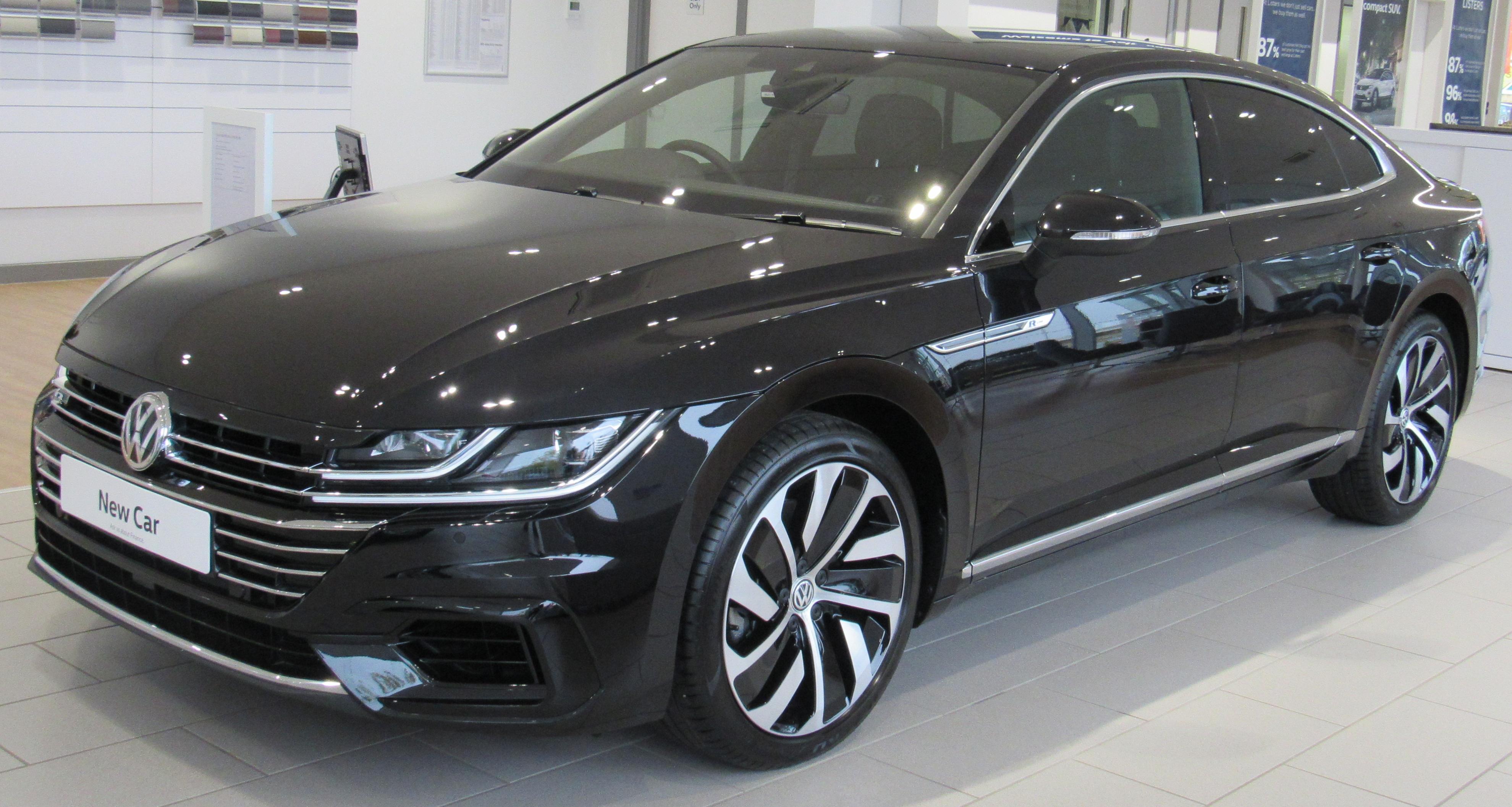 Volkswagen sedan, black, in an auto sales showroom