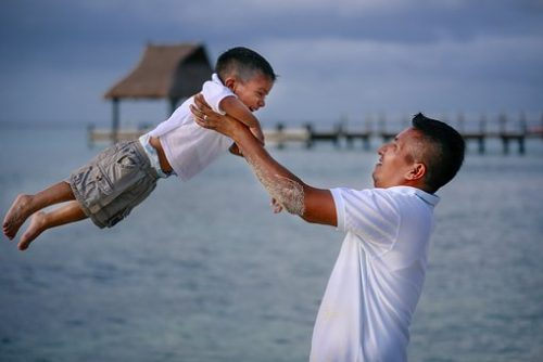 father lift his son up on the beach