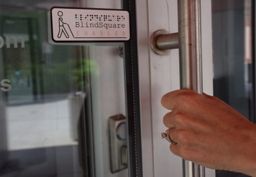 photo of BlindSquare sign on a glass door with a hand on the door handle