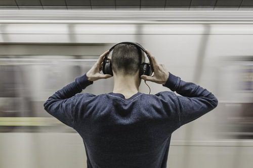 photo of man with headphones on from the back