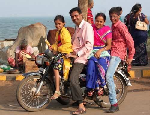 A family packs onto a motorcycle in India for a photo
