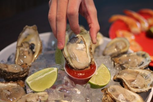 Hand of person dipping raw oyster into red sauce