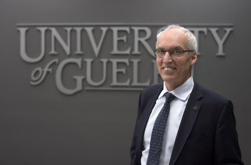 photo of U of G president Franco Vaccarino in front of a University of Guelph sign