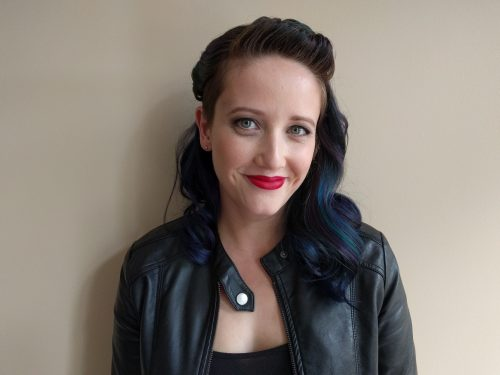 Jessica Wood smiling a bit wearing a leather jacket