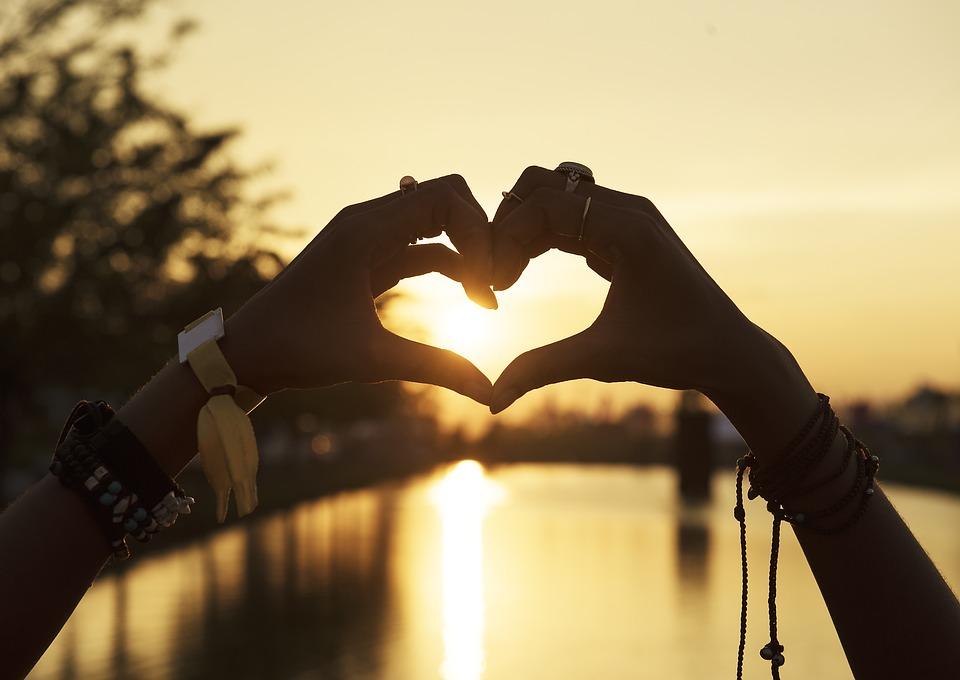 hands making heart shape in beach scene at sunset