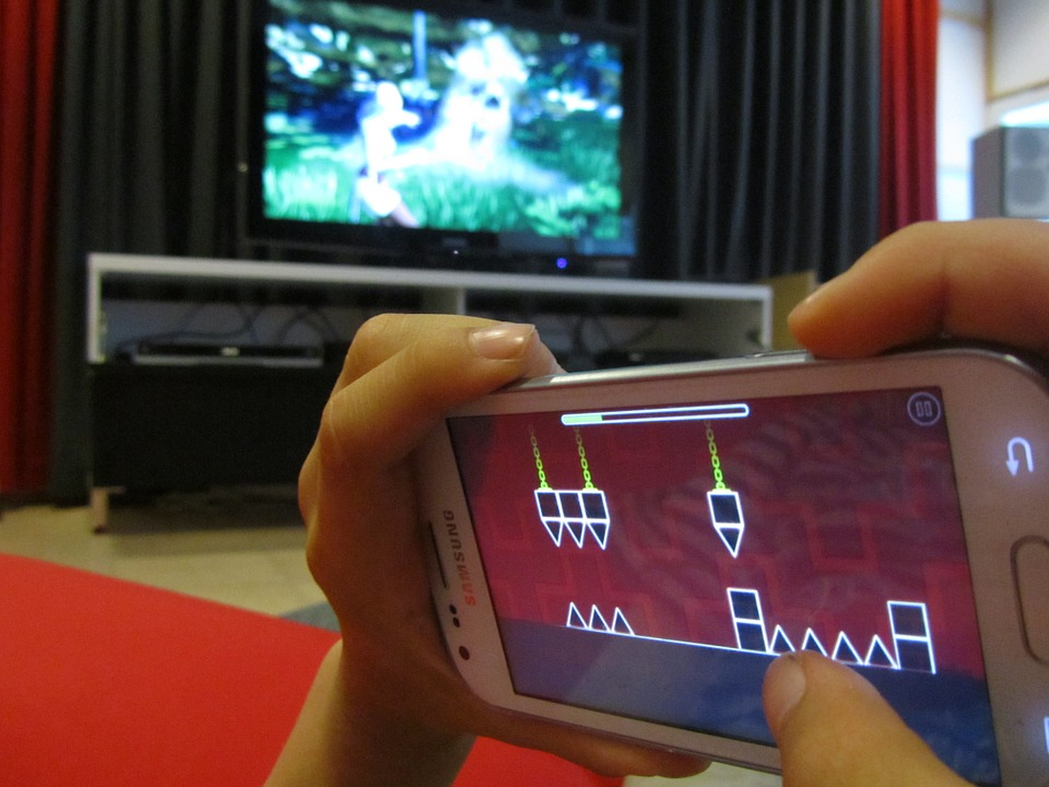 kids hands on phone playing video game with massive TV screen in background