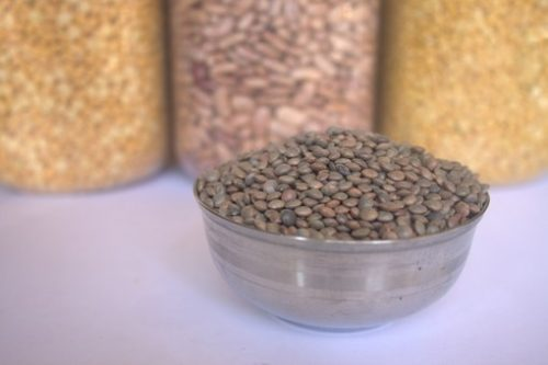 photo of a bowl full of lentils with canisters of different pulses in the background