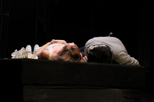 Scene from Romeo and Juliet on stage in darkness - they are both dead