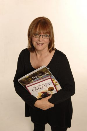 Anita Stewart holding an armload of cookbooks