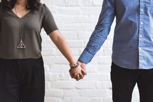 Couple holding hands but standing apart facing forward
