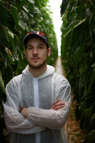 Dylan Sher, arms crossed, wearing baseball cap standing in tractor bay