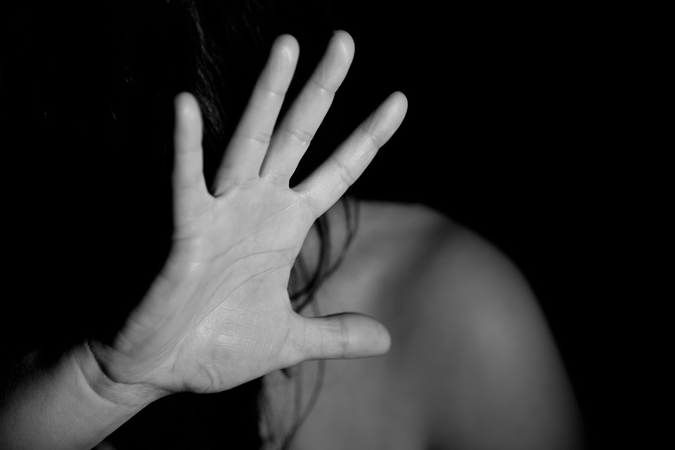 image of a woman holding her hand up to shield her face