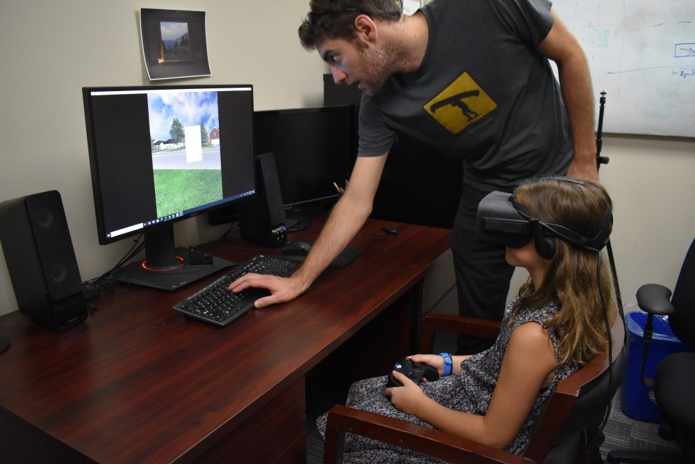 662d98b0a9e8 A young girl uses VR goggles and gaming console to play game that teachers  her how