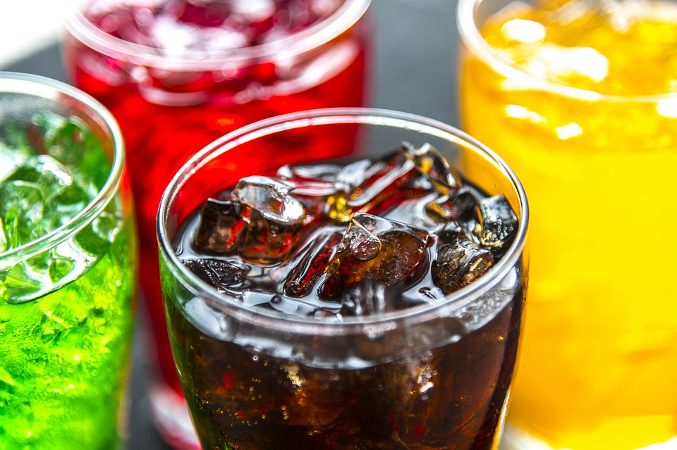 glasses of different types of sodas with ice cubes