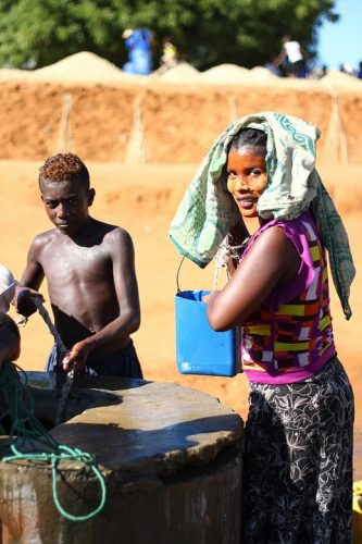 boy and woman collecting water from a well in Madagascar