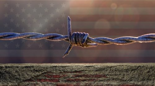 american flag with barbed wire fence across