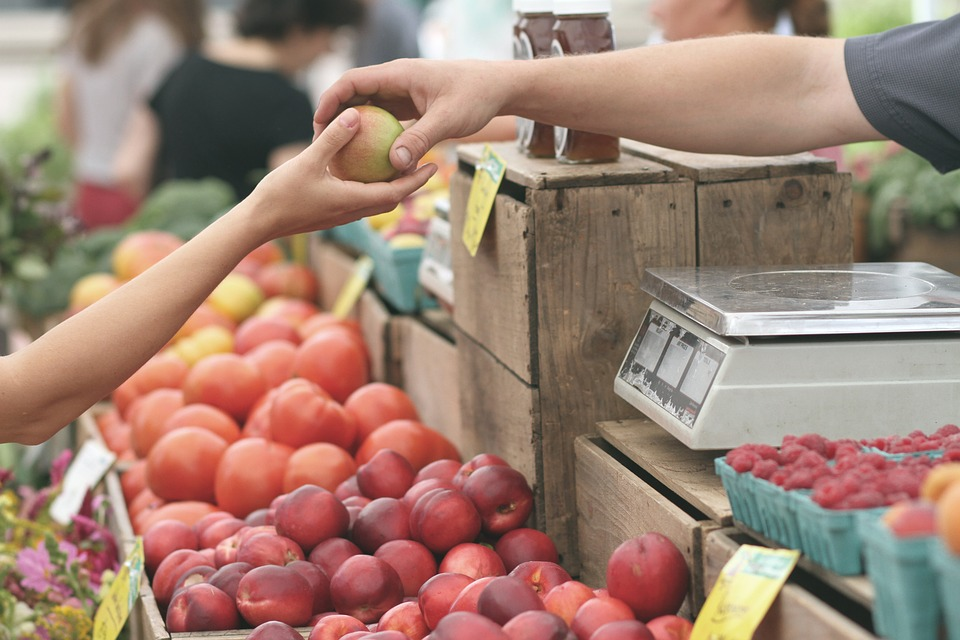 farmers market stall, customer's hand reaching over stacks of fruit to pass an apple to a vendor at the market