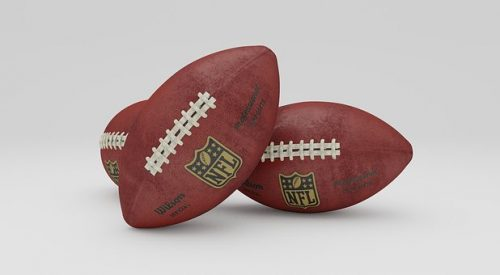 photo of three NFL footballs leaning against one another