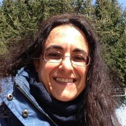 headshot of Prof. Elena Choleris infront of an evergreen tree