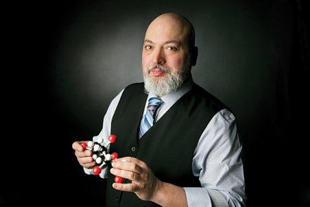 photo of Prof. Mario Monteiro holding a model of molecules