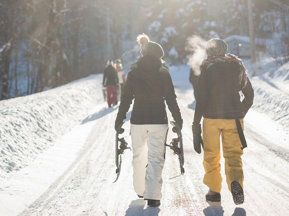 two women wearing ski gear walking in snow at ski resort