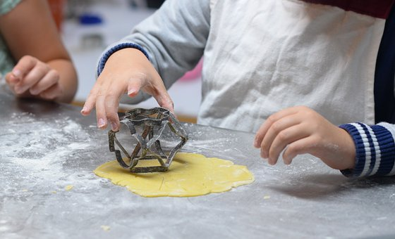 image of a child's hand pushing shaped cutters into dough