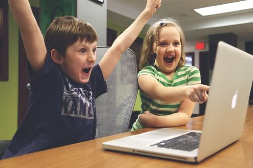 two kids pointing at a computer screen