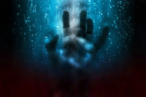 image of a hand pushed against glass surrounded by water, with a faded face in the background