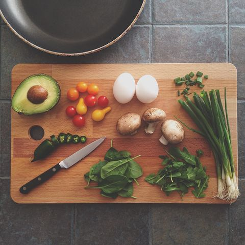 photo of vegetables, avocado, egg on a wooden cutting board with a knife