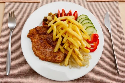a dinner plate with meat and fries