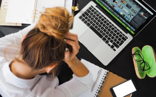 A photo of woman at a desk holding her head in her hand