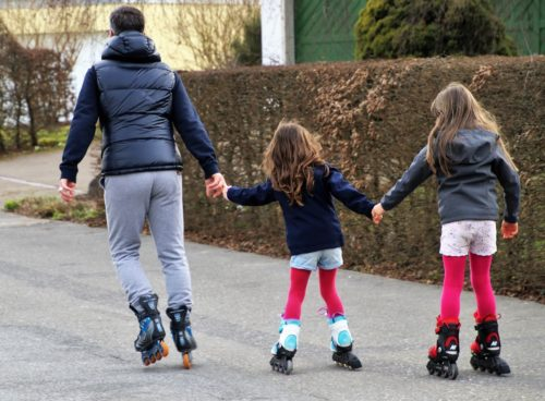 A dad and two daughters roller blading