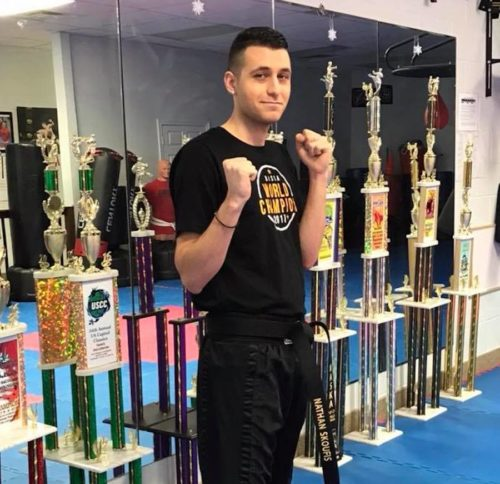 Martial artist with raised fists in front of row of trophies.