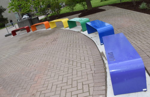 Six rainbow-coloured benches