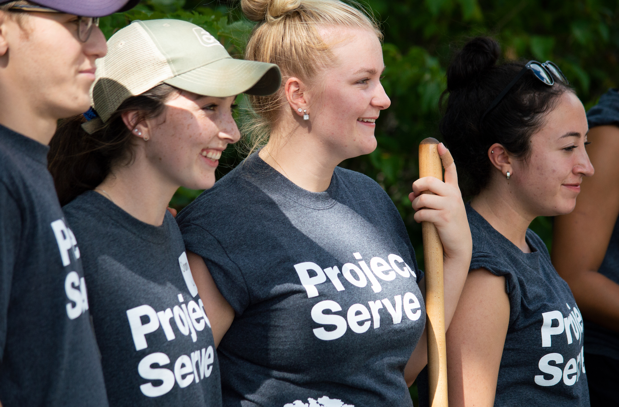 Four volunteers in Project Serve Day t-shirts are shown in this photo.