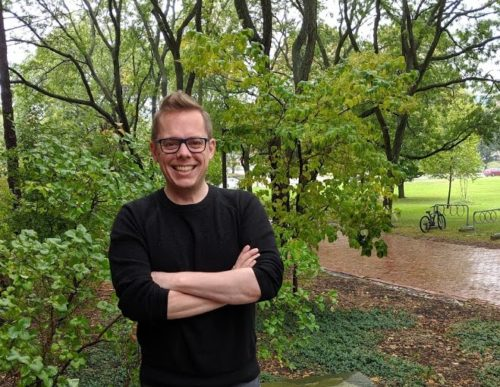 Professor with folded arms in outdoor campus setting