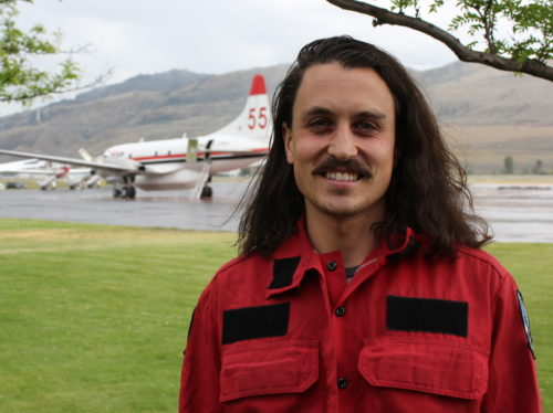 Man with long hair and moustache outdoors along an air strip